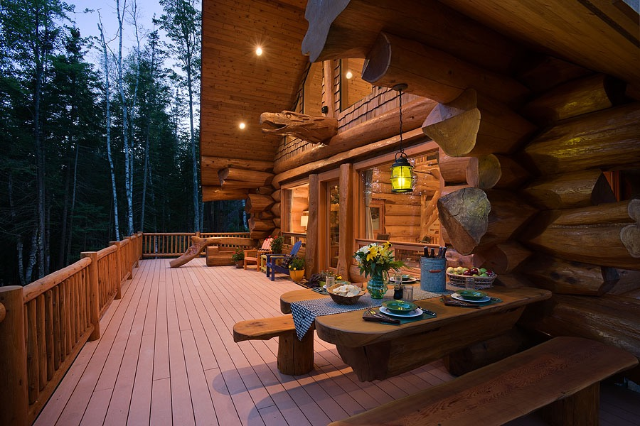 Exterior, horizontal, deck with built in log dining table set for dinner at twilight